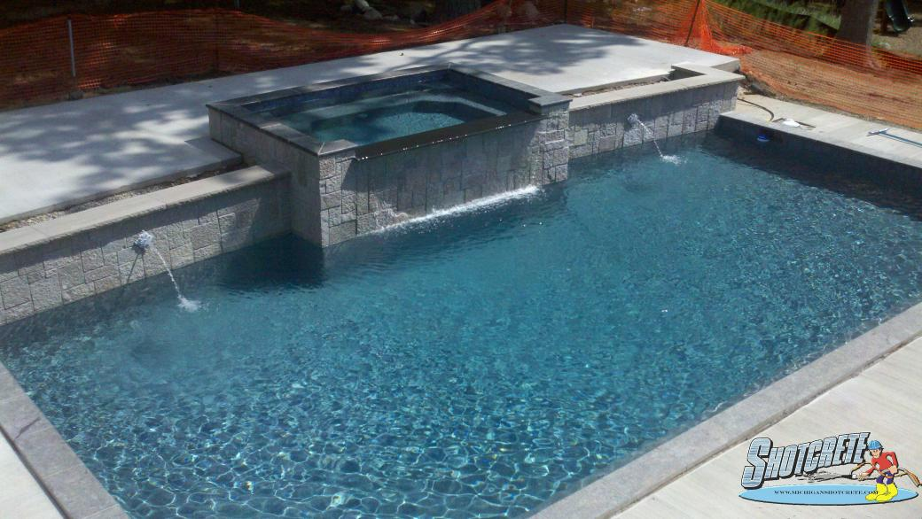 Custom pool in Milford, Mi Spillover spa and pebble coating