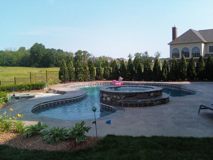 swimming pool with round stone covered spill over hot tub. Stamped concrete patio with step down fire pit. Pool features bluestone pool coping, cantilevered, sun shelf, deep-end bench, and colored led lights in Northville, Mi